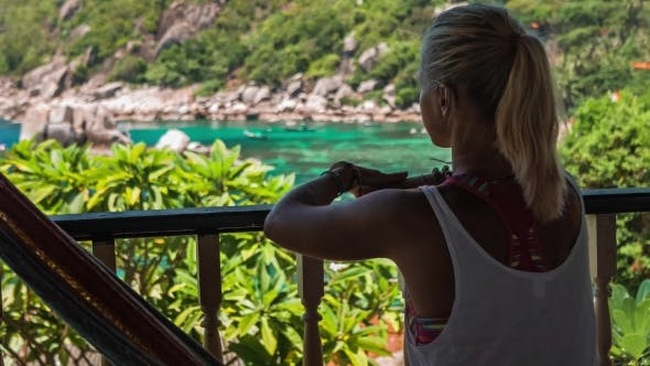 Thumbnail for Girl Sitting in Hammock on an Terrace and Showing with Her Hand the Beautiful Tanote Bay, Koh Tao