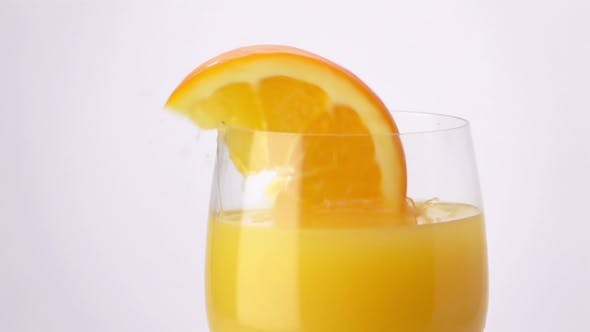 Thumbnail for Slice of Orange Falling into a Glass of Orange Juice.