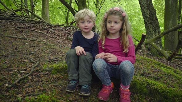Two Kids Sitting Together In The Woods