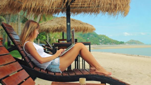 Thumbnail for Young Woman Freelancer Sitting at the Sunbed with a Laptop
