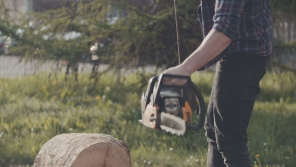 Thumbnail for Young Man Cutting Wood With Chainsaw In Yard