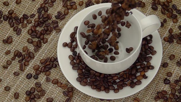 Thumbnail for Ganze Kaffeebohnen fallen in die Tasse.