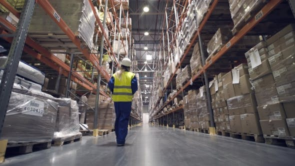 Warehouse Worker Walks Through Rows of Warehouse
