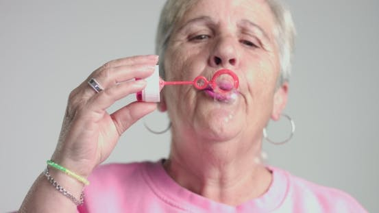 Thumbnail for Eldery Woman Blow Bubbles To Camera