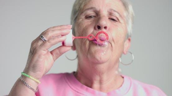 Eldery Woman Blow Bubbles To Camera