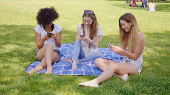 Thumbnail for Women Using Smartphones on Meadow