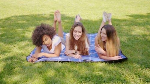 Happy Female Friends Lying on Grass
