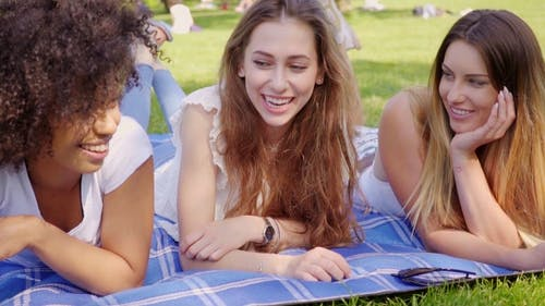 Cheerful Young Girls Lying on Lawn