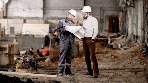 Der Ingenieur zeigt dem Kunden in einem Schutzhelm die Schätzung eines Neubaus, um