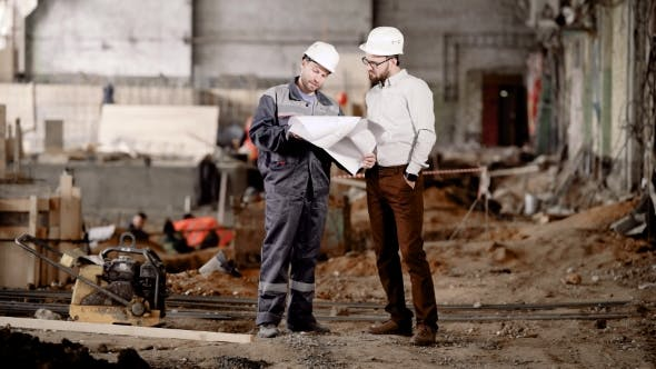 Thumbnail for The Engineer Shows the Customer in a Protective Helmet the Estimate of a New Building in Order To