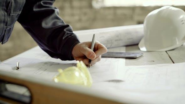 Thumbnail for Der männliche Ingenieur macht Anpassungen an den Baustellenzeichnungen, er ist im Gebäude von