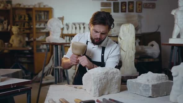 Thumbnail for Master Sitting in the Craft Studio and Knocking off Limestone the Future Sculpture Using Hammer