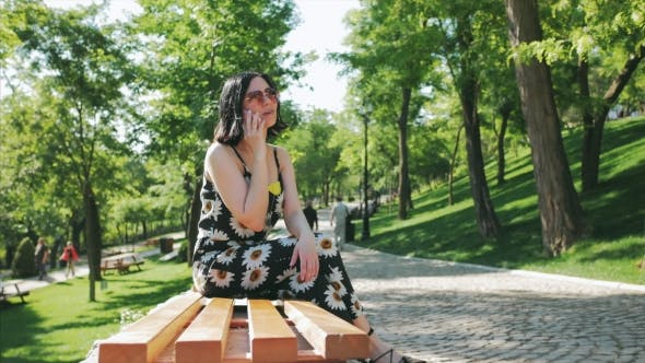 Thumbnail for Beautiful Young Girl in Park Talking To Mobile. Portrait of a Happy Caucasian Brunette Woman Smiling