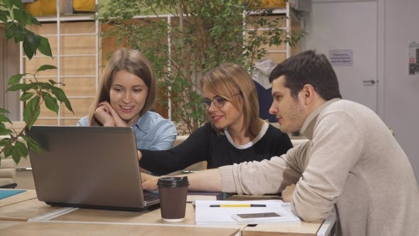 Thumbnail for Young Man Shows His Coworkers Something on Laptop at the Working Hub