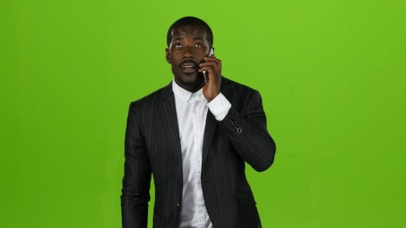 Thumbnail for Businessman Takes the Phone and Starts Talking on the Phone. Green Screen