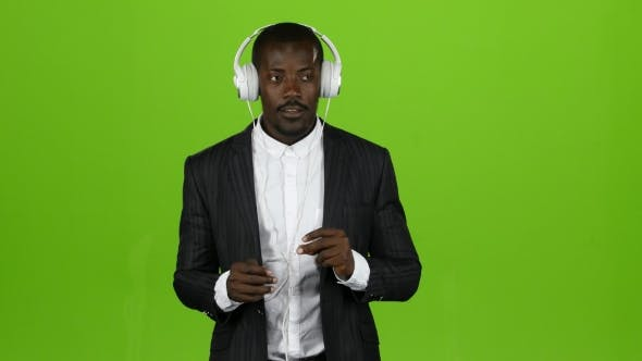 Thumbnail for Black African Guy Listens To Music Through Headphones and Sings Along. Green Screen