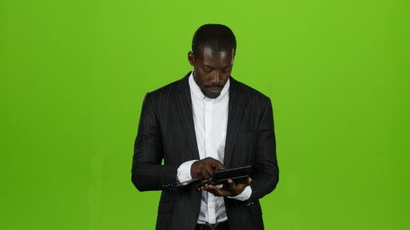 Thumbnail for African Businessman Calculates His Income on a Calculator, He Smiles. Green Screen