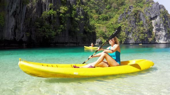 Cover Image for Woman Paddling a Kayak in the Island Lagoon Between Mountains. Kayaking in El Nido, Palawan