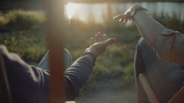 Thumbnail for of Two Lovers Man and Woman Joining Hands Over the Sunset Lake Background, Move Camera