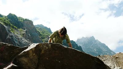 Man Climbs a Boulder and Raises His Hands Up. Bouldering in the Mountains