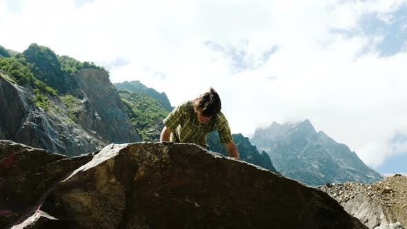 Thumbnail for Man Climbs a Boulder and Raises His Hands Up. Bouldering in the Mountains