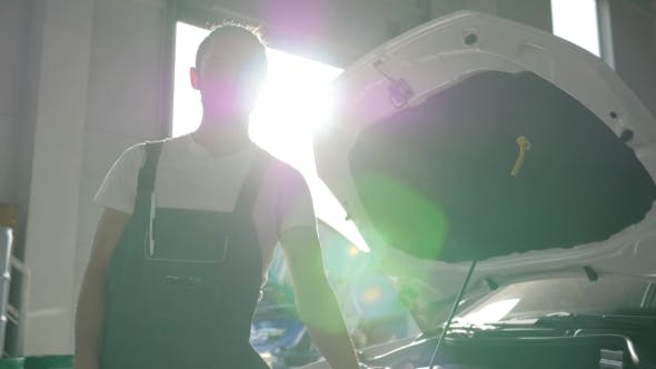 Thumbnail for Portrait Master on Service Station, Machine Mechanic in Backlight Near Opens Bonnet, Man in Overalls