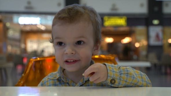 Thumbnail for Young Boy Eating French Fries at the Food Court