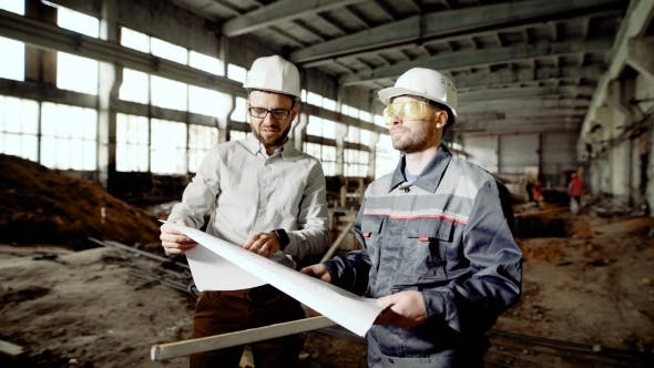 Thumbnail for Foreman and Chief Engineer at the Construction Site of the Factory. The Engineer Checks the Drawing