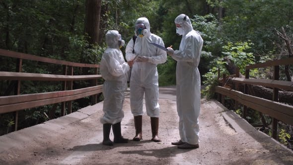 Thumbnail for Three Men in Biohazard Suits Standing on a Bridge