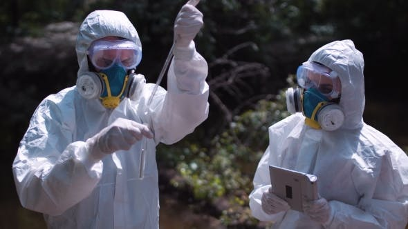 Thumbnail for Two Men in Biohazard Suits Sampling Water