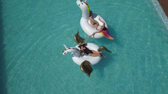 Thumbnail for Aerial - Schöne Mädchen in einem Bikini auf einer aufblasbaren Pegasus und Einhorn-Matratze im Pool