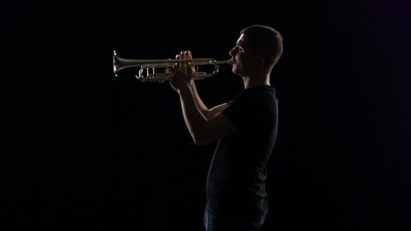 Thumbnail for Trumpeter Man Plays on Wind Instrument Melody. Black Studio Background