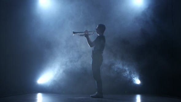 Thumbnail for Trumpeter Man in Smoky Studio and in Spotlight Playing Melody