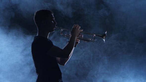 Cover Image for Professional Musician Man Playing on Trumpet. Smoky Isolated Studio, Silhouette