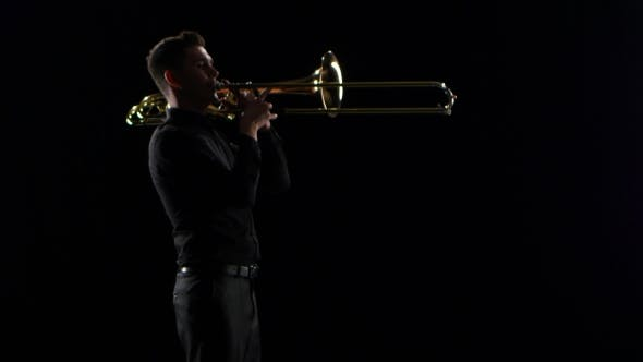 Cover Image for Trumpeter Plays on Wind Instrument Tranquil Melody. Black Studio Background