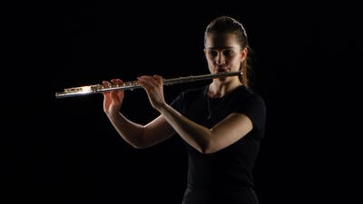 Female Plays on the Flute Classical Melodies. Black Studio Background