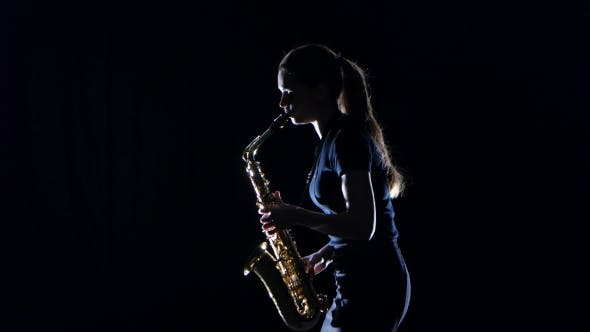 Thumbnail for Female Musician Playing on Saxophone Standing Sideways on Black Studio