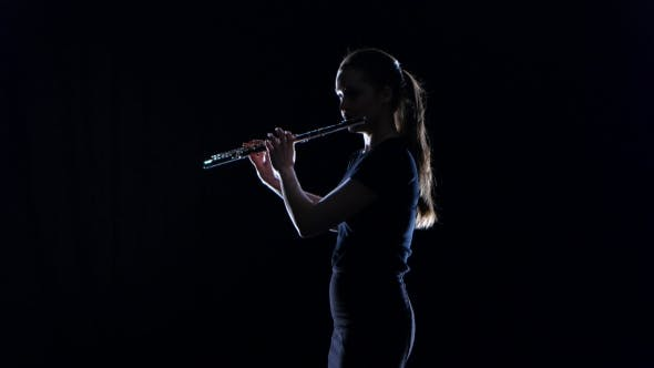 Thumbnail for Woman Musician Blows the Motif in Wind Instrument. Black Studio