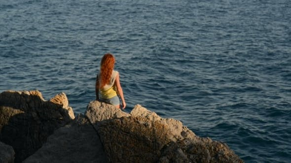 Cover Image for Young Woman with Flying Hair Sitting on a Rocky Seashore