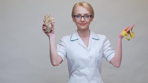 Thumbnail for Nutritionist Doctor Healthy Lifestyle Concept - Holding Ginger Root and Measuring Tape