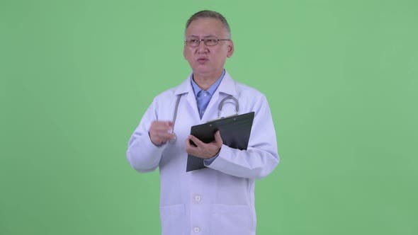 Thumbnail for Happy Mature Japanese Man Doctor Explaining While Holding Clipboard