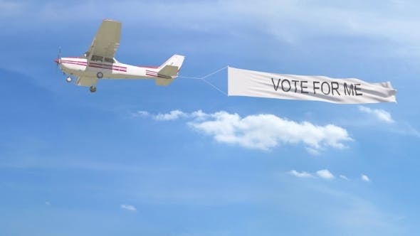 Thumbnail for Small Propeller Airplane Towing Banner with VOTE FOR ME Caption in the Sky