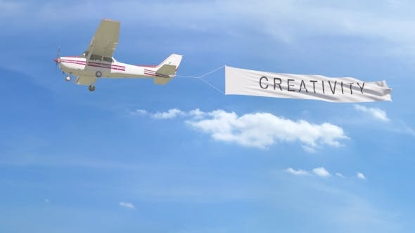 Thumbnail for Small Propeller Airplane Towing Banner with CREATIVITY Caption in the Sky