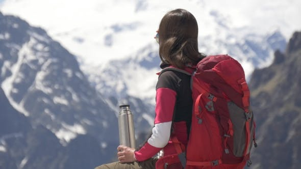 Thumbnail for Woman Drinking Tea Form Thermos High in Mountains