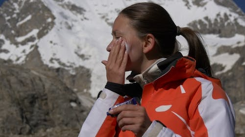 Woman in Mountains Applying Sunscreen