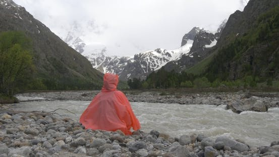 Thumbnail for Person in Raincoat Sitting Near Mountain River