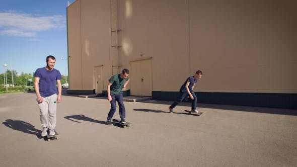 Thumbnail for A Few Friends Go on a Skateboard on the Asphalt Near the House, Men Ride on the Boards in the Summer