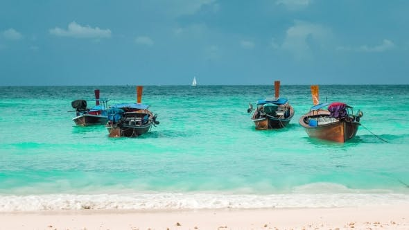 Thumbnail for Four Long-tailed Boat Swinging in Blue Waves on Bundhaya Beach, and White Sail Boat on the Horizon