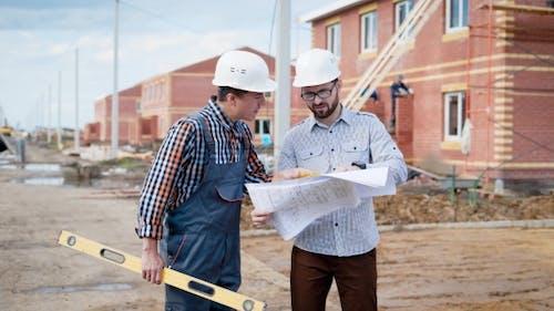 Team von Bauherren bei der Arbeit. Baumeister und Baumeister mit Gebäudeebene