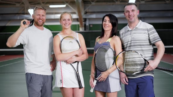 Thumbnail for Happy Married Couples in Sports Clothes Stand in a Tennis Club with Rackets in Their Hands, Men and